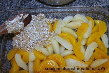 spooning topping of peach pear crisp