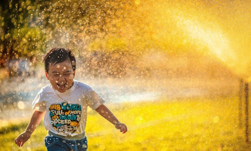 Inexpensive summer activities: enjoy an afternoon of sprinkler fun.